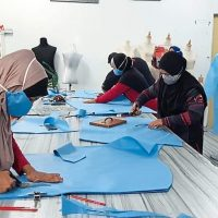 The Cancer Survivors Malaysia (CSM) cutting up the non-woven material to make personal protective equipment (PPE) suits and head covers at a centre in Kedah.